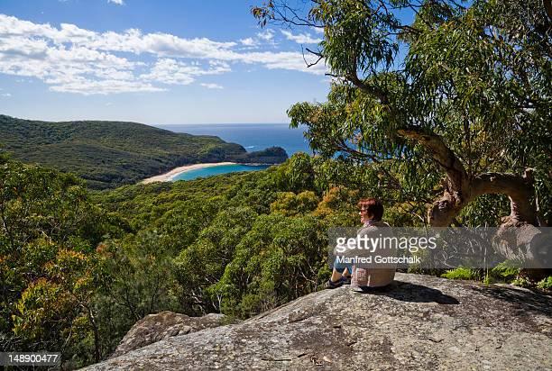 Woman on rock in bushland on slopes of Bouddi Ridge at Maitland Bay.