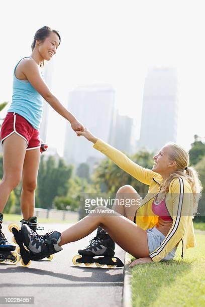 Femme aidant un ami sur rollerblades depuis le rez-de-chaussée
