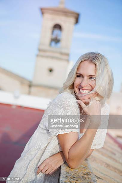 Woman on rooftop, bell tower in background