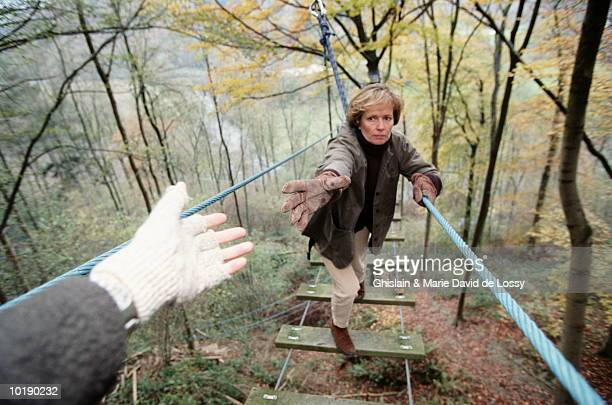 Woman on rope bridge, reaching out to another woman