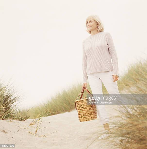 Woman on sandy beach with picnic basket