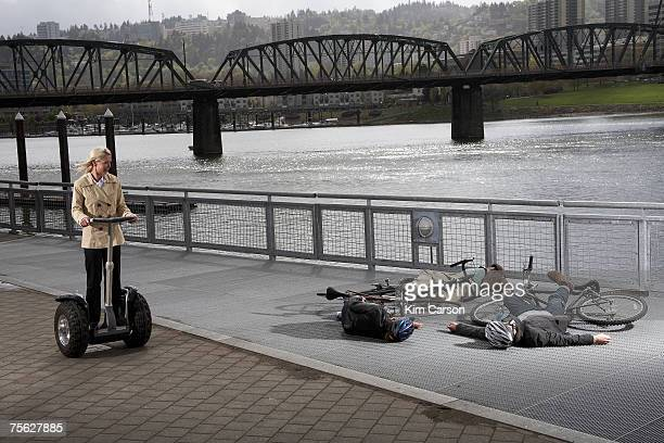 Woman on segway riding past two men and woman with bicycles lying on pavement by river
