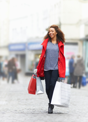 Woman on shopping street with gift bags.