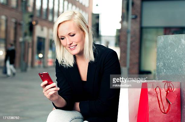 Woman on shopping trip looks at her phone