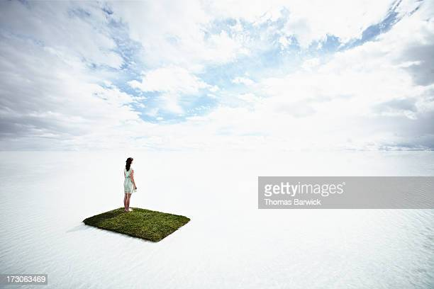 Woman on small grass island in large body of water
