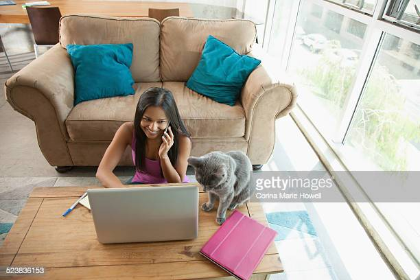 Woman on smartphone using laptop at home