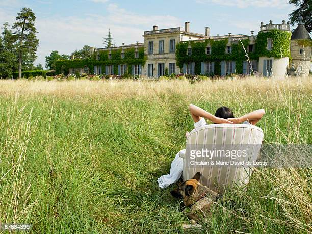 Woman on sofa in a field,  castle view
