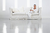 Woman on Sofa in Sleek White Room