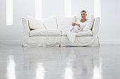 Woman on Sofa in Sleek White Room