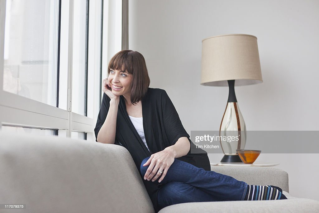 Woman on sofa looking out window, relaxing : Stock Photo