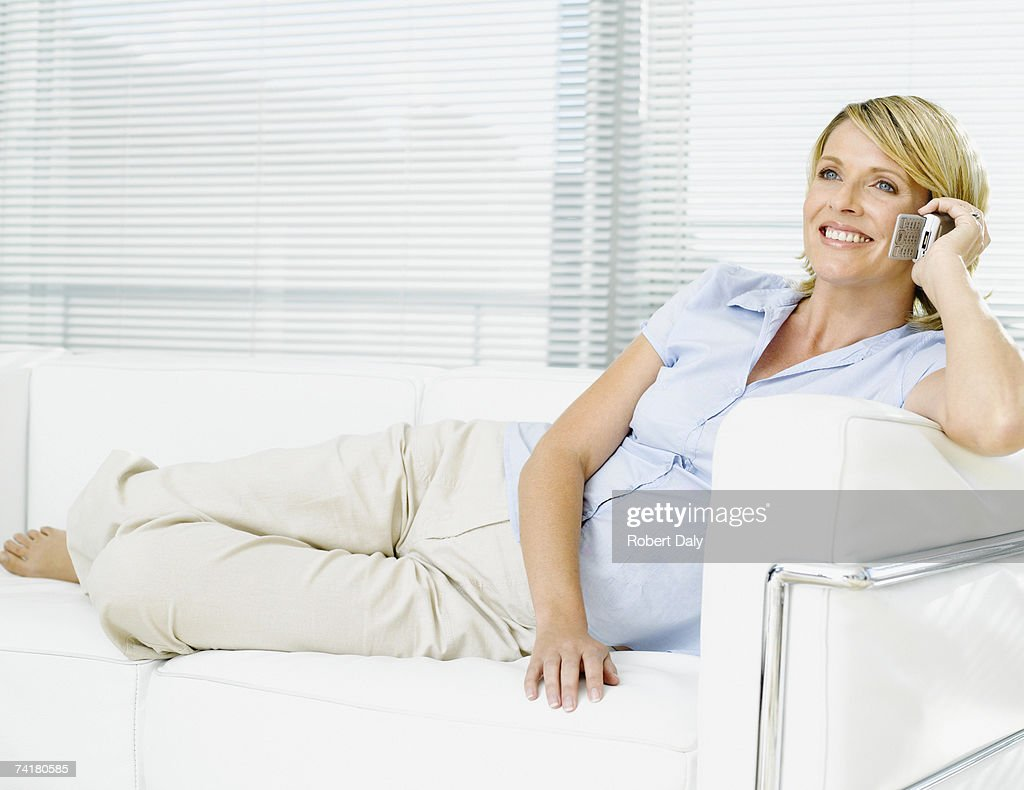 Woman on sofa talking on cell phone : Stock Photo