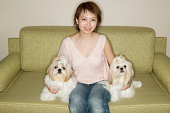Woman on sofa with Pekinese dogs