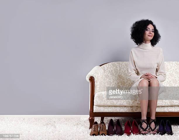 Femme sur le canapé avec une gamme de chaussures. Papier peint