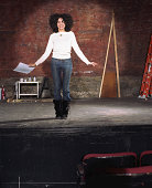 Woman on stage in theater, smiling