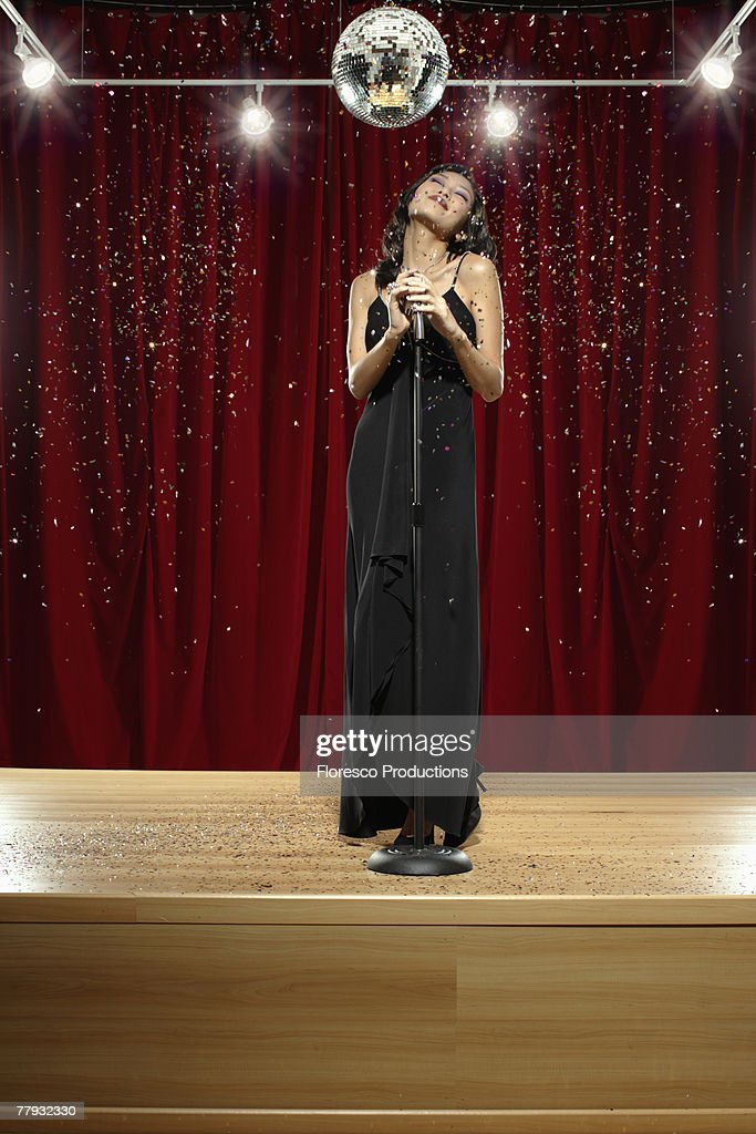 Woman on stage with microphone and confetti : Stock Photo