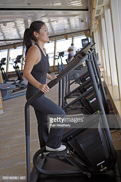 Woman on stair climbing machine in health club, side view