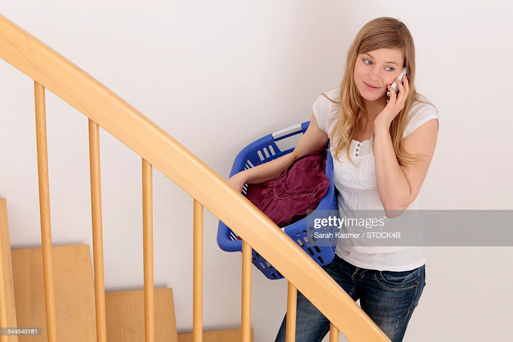 Woman On Stairs With Laundry Basket And Cell Phone : Stock Photo