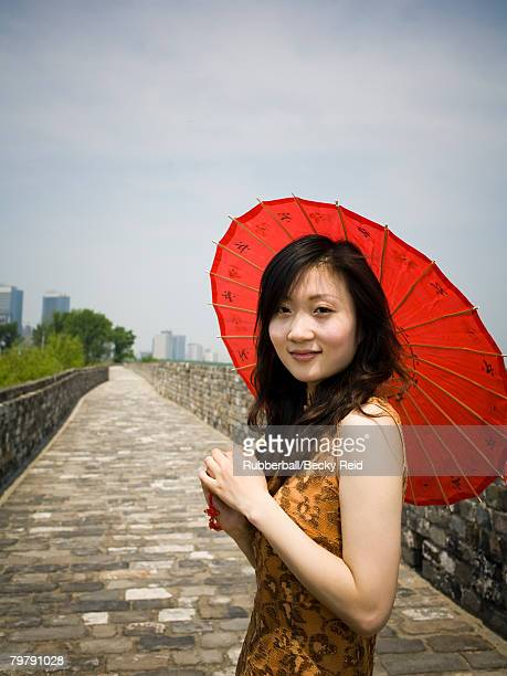 Woman on stone bridge with red parasol