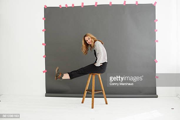 Woman on stool in front of photographers backdrop