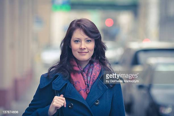 Woman on street wearing coat and scarf
