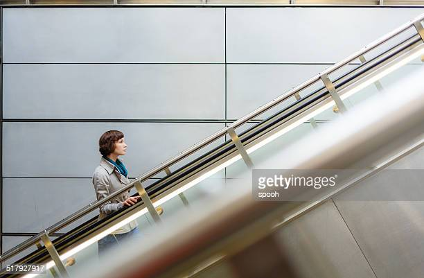 Woman on subway station escalator in Copenhagen, Denmark.