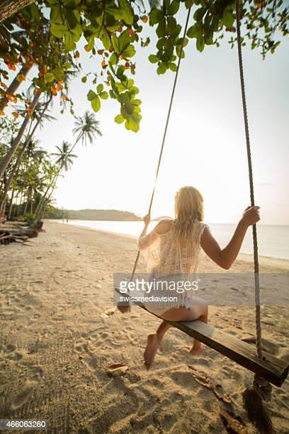 Woman on swinf watching sunset at beach