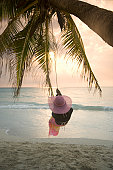 Woman on swing at beach, rear view, sunset