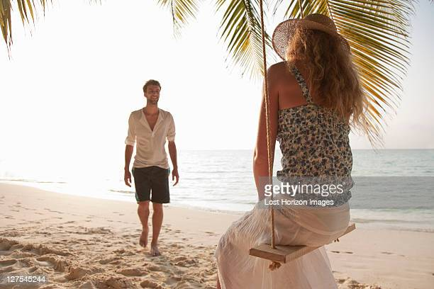 Woman on swing with boyfriend at beach