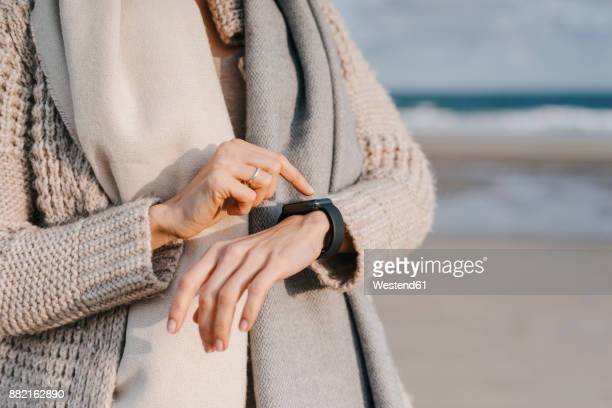 Woman on the beach checking her smartwatch