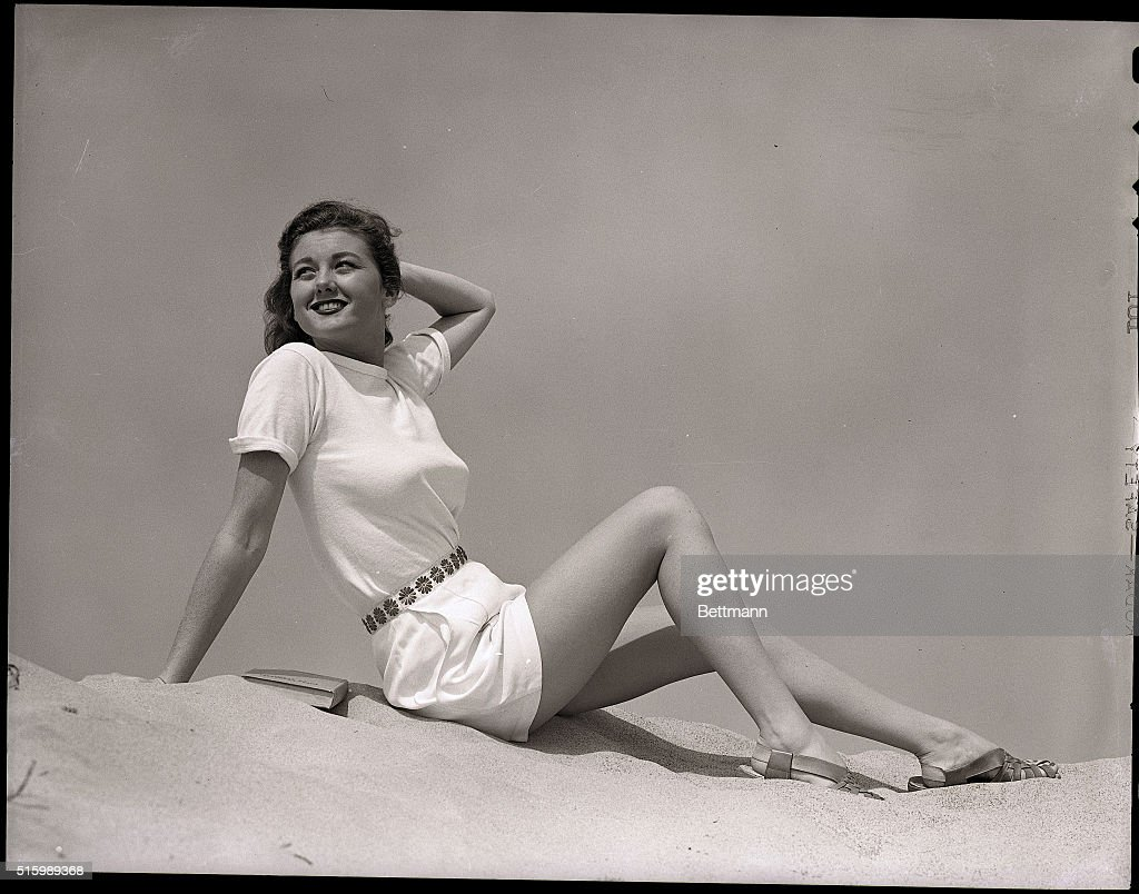 Woman on the beach in cheesecake pose wearing white teeshirt and shorts with embroidered flower waistband and sandals Ca 1940s