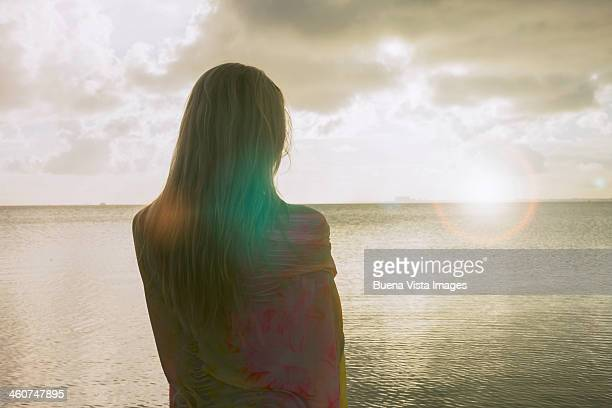 Woman on the beach watching the horizon