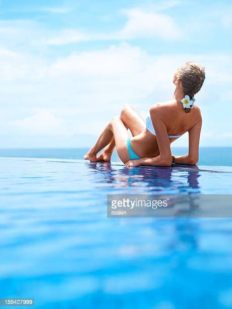 Woman on the edge of infinity pool
