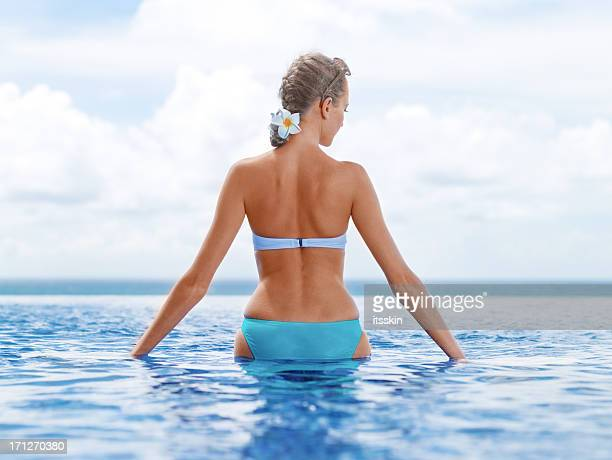 Woman on the edge of infinity pool