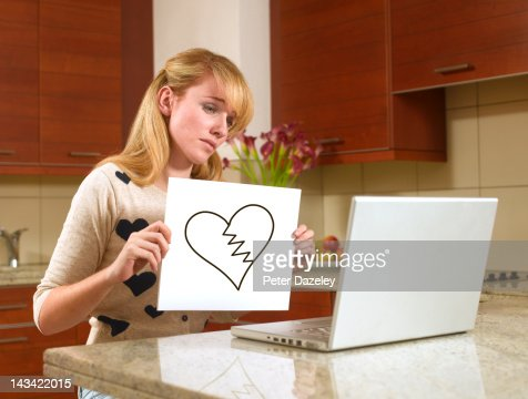 Woman on the internet with a broken heart sign : Stock Photo