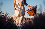 Woman in white dress running on lavender field with basket of flowers in her hands