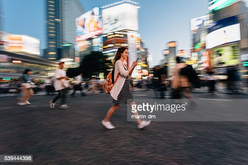 Woman on the phone at Shibuya crossing in Tokyo