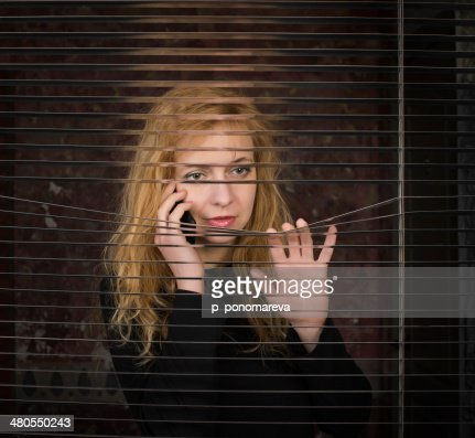 Woman on the phone looking through venetian blinds : Stock Photo