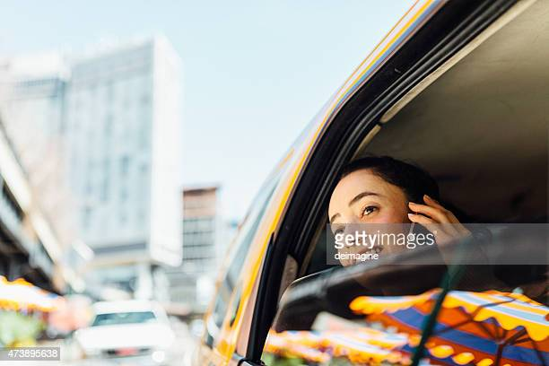 Woman on the phone while traveling by taxi