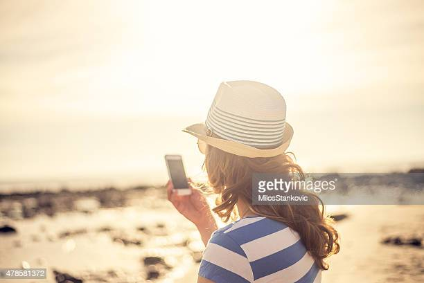 Woman on the sea at sunrise with mobile phone