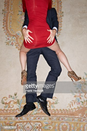Woman on top of man on carpet : Stock Photo