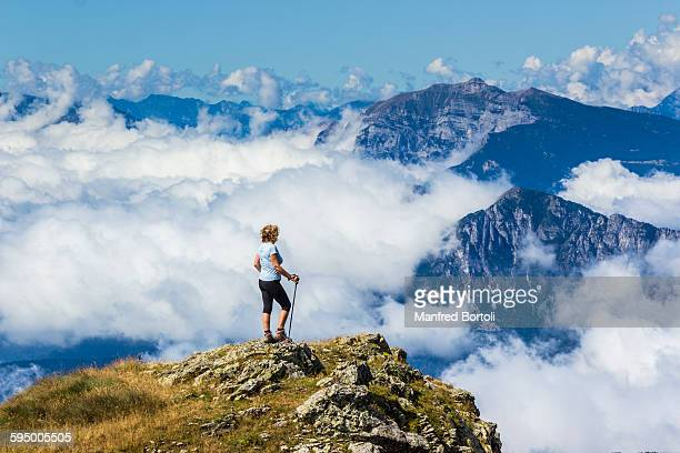 Woman on top of mountain with a carpet of clouds