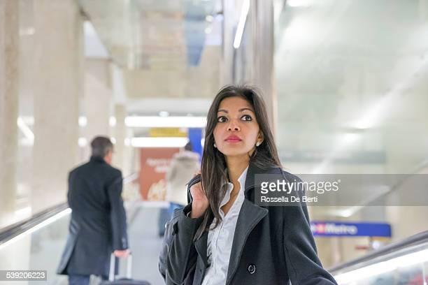 Donna su tapis roulant alla stazione centrale di Milano