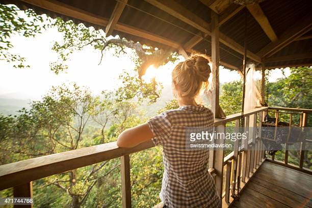 Woman on tree house looking at sunset