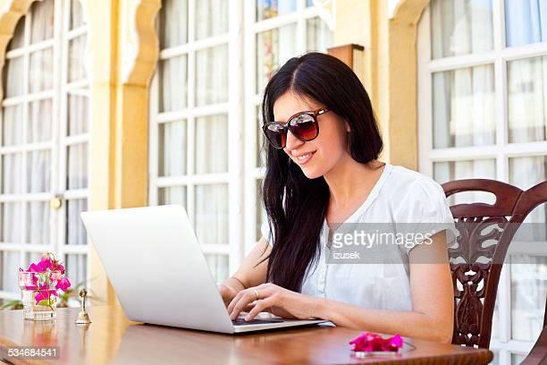 女性トロピカルなバケーションのノートパソコンを使う