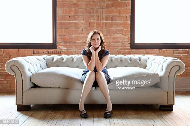 Woman on tufted sofa