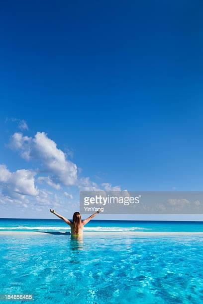Woman on Vacation enjoying Infinity Pool in Caribbean Resort Hotel