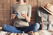 Young woman on vacations using phone and credit card. Online shopping concept