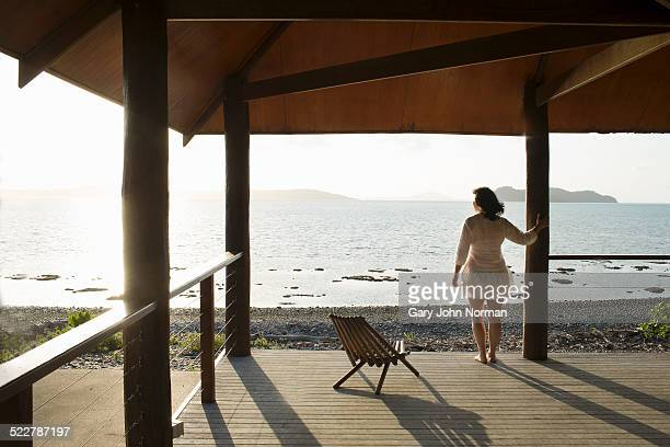 Woman on veranda looking out to sea.