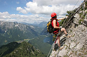 woman climbing on via ferrata to the peak of pfaffenstein. In the background lake named leopoldsteinersee near eisenerz in styria, austria