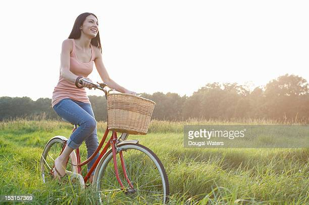 Woman on vintage bike in meadow.